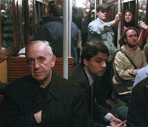 Cardinal Bergoglio on a public bus, accompanied by Federico Wals (his press secretary and personal assistant). Wals is the young man sitting directly behind Bergoglio.